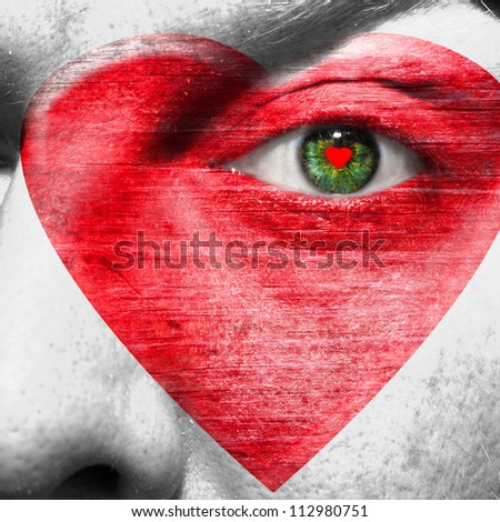 Red heart painted on white face with heart shaped red pupil in a green eye