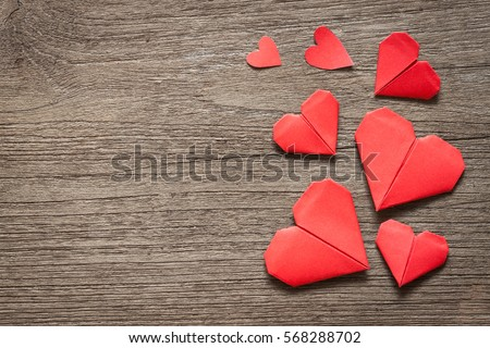 Red heart paper origami on wooden background, valentine's day and romance concept