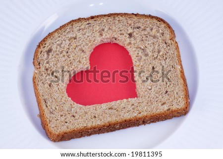Red heart pattern cut in a slice of whole grain bread, on a white plate.