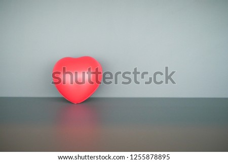 Red heart shape ball infront of gray background. #1255878895
