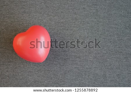 Red heart shape ball on gray fabric background. #1255878892