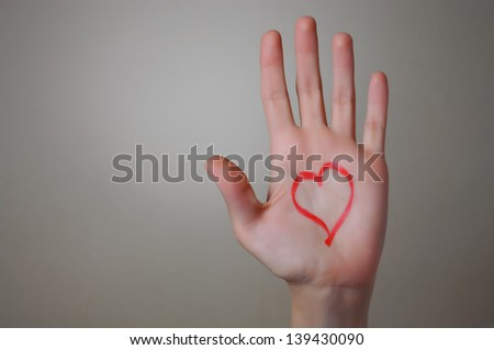 Red heart shape drawn on woman's palm with lipstick