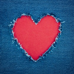 Red heart shape for copy space torn from blue denim jeans fabric, romantic love concept background