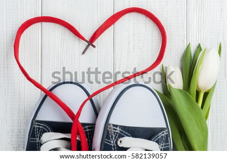 Red heart shape from laces and blue sneakers on white wooden background, Healthy fitness  concept  #582139057