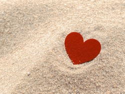 red heart shape on sand