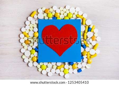 Red Heart Shape with a Pills on the Table closeup #1253405410
