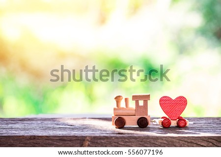 Red Heart Shape with Wooden Toy Train on wooden floor over blurred green garden  background,Image to Valentine Day concept. #556077196
