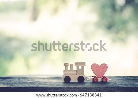 Red Heart Shape with Wooden Toy Train on wooden floor over blurred green garden  background,Image to Valentine Day concept. #647138341