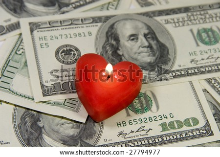 Red heart-shaped candle on a pile of US dollars (Love for Money concept)
