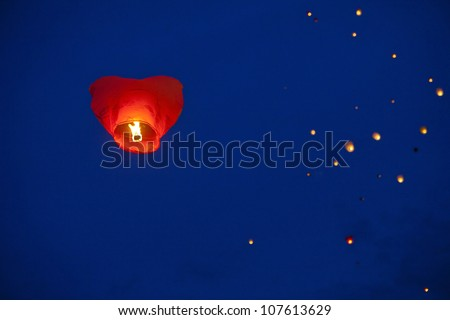 Red heart-shaped chinese lantern in the night sky - stock photo