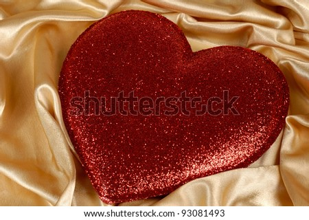 Red heart-shaped cushion on golden fabric background