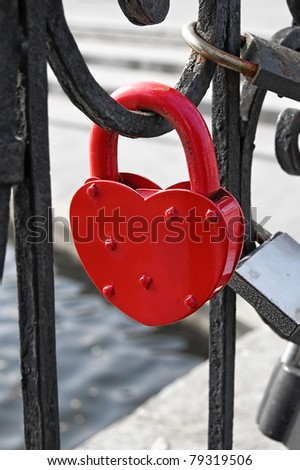Red heart-shaped lock on the fence on the background of other castles, water, concrete pavement
