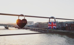 Red heart shaped love lock Always and forever sign symbol british flag padlock on Millennium bridge railing Thames river London England Great Britain GB, United Kingdom UK Europe