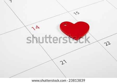 Red heart sign laying on calendar page points St. Valentine's day