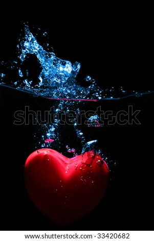 red heart splashing on water against black background