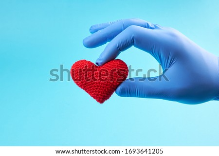 red heart symbol at persons hand  with blue medical gloves on. light blue background with copy space. heart disease concept. Сток-фото ©