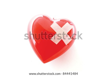 Red heart with adhesive plaster isolated on white background