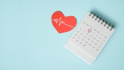 red heart with heartbeat and white calendar page with circle marked on 1st date on grunge blue background for appointment or reminder , health and medical concept , world heart day, health checking