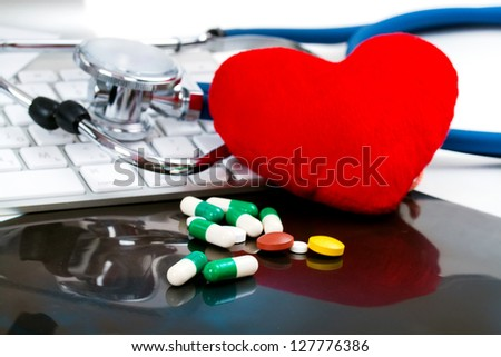 red heart, with pills, tablets, capsule, stethoscope and keyboard on black roentgen, x-ray