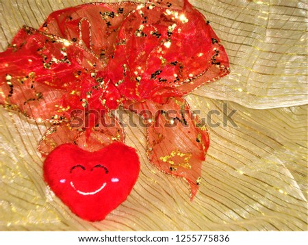 Red heart with red bow on a glittery golden background. Valentine day greeting card. Free space for text. #1255775836