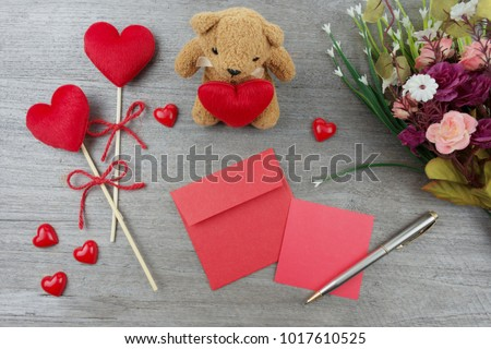 Red heart with red ribbon stick. A brown bear holds a red heart. Red paper note, silver pen and flower placed on wooden board. Flat lay. #1017610525