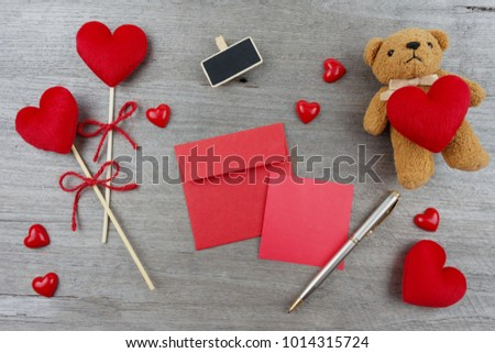 Red heart with red ribbon stick. A brown bear holds a red heart. Red paper note, silver pen placed on wooden board.  #1014315724