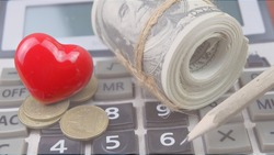 Red heart with roll of banknote on calculator.Concept for saving money for health.