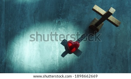 Red heart with wood crucifix on grey marble. Concept Jesus loves you, Jesus crucify himself on cross with love. Forgiving sin , God's love, Easter time , Faith God. Christianity background.
