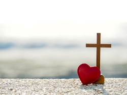 Red heart with wooden Christian cross on gravel floor in morning light, beach sea as background. Jesus love you. Faith hope believe in God. Believe in salvation. Christianity background concept.
