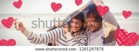 Red Hearts against happy young couple taking selfie during winter