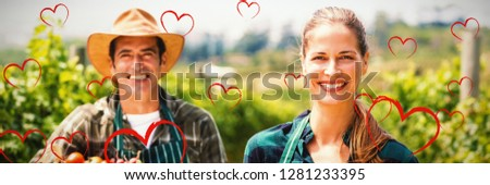 Red Hearts against portrait of happy farmer couple holding baskets of vegetables and fruits
