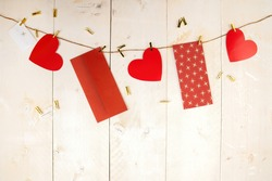 Red hearts and envelopes hanging on cord on wooden background. Postcards with love symbols on white wood with copy space. Horizontal backdrop with valentine themes.
