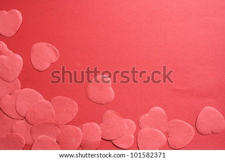 Red hearts confetti on red background