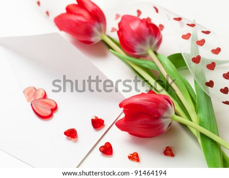 Red hearts on a letter and tulips for Valentines Day - stock photo