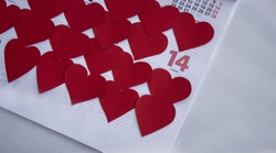 Red hearts on February Calendar 2021. 14th February marked with hearts. Valentine's Day Concept close up.