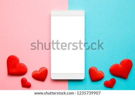 Red hearts on pastel blue and pink paper. Love through modern devices. Top view. Mockup for positive idea. Empty place for lovely, emotional, sentimental text, quote or sayings on white mobile screen. #1235739907
