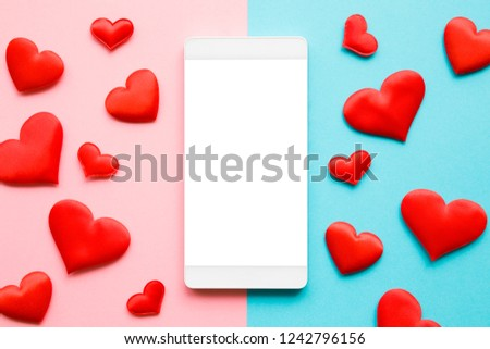 Red hearts on pastel blue and pink paper. Love through modern devices. Top view. Mockup for positive idea. Empty place for lovely, emotional, sentimental text, quote or sayings on white mobile screen. #1242796156