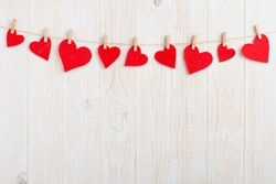 Red hearts on rope with clothespins, on a white wooden background. Place for text, copy space.