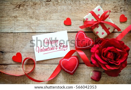 Red hearts, rose, ribbon, message card and gift box on wooden table. Valentines Day background #566042353