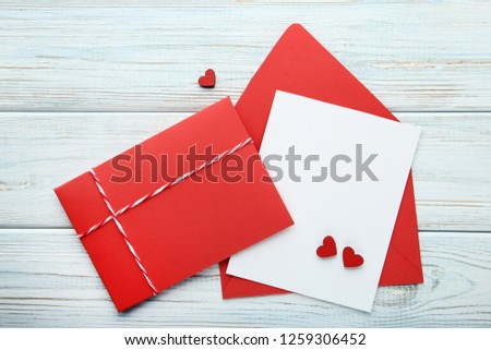 Red hearts with red envelopes and blank sheet of paper on wooden table #1259306452
