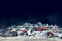 Red heat in a bonfire. Scattered pieces of embers in the hearth mixed with ash.