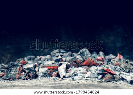 Photo of  Red heat in a bonfire. Scattered pieces of embers in the hearth mixed with ash.