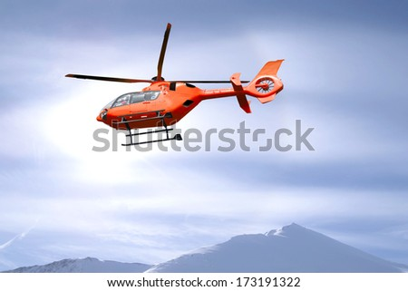 Red helicopter flies over snow capped mountain summits