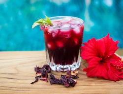 Red hibiscus herbal ice tea beside red hibiscus flower and dried herble tea on wooden table with swimming pool view background.