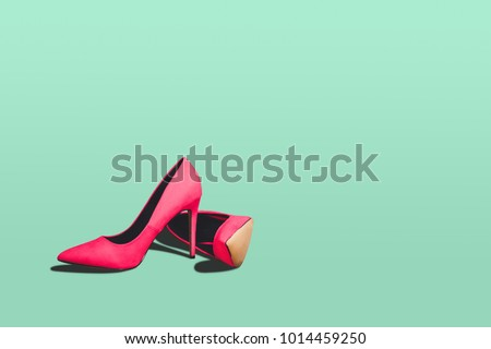 Red high heels isolated on a bright green pastel background. Fashion concept, catwalk. A modern and fashionable shoe store. #1014459250