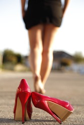 Red high heels standing on the street an a woman goes away barefoot