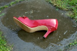 Red highheel abandoned on the asphalt, wet after rain, outdoor close-up