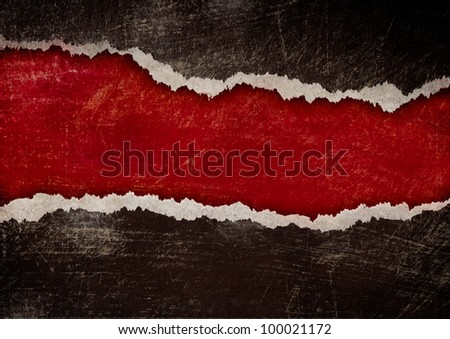 red hole with torn edges in black grunge paper