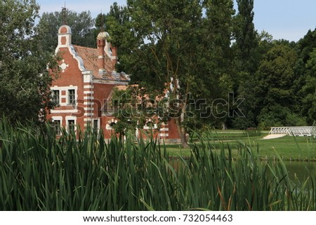 Red Holland house (A Holland Ház) with reeds on isle in garden of Classicist manor house in Dég, Hungary  Stock fotó ©