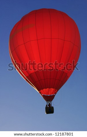 Red hot air balloon illuminated by sunrise against blue sky